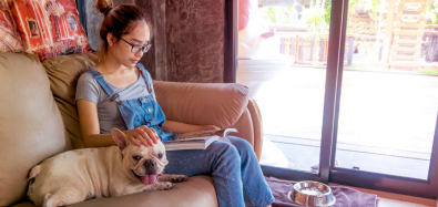 girl reading with dog on couch